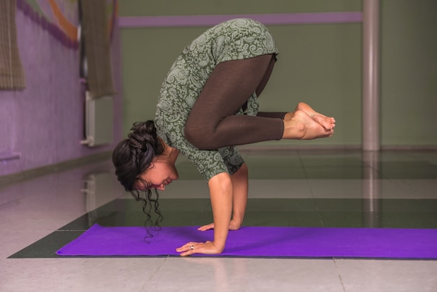 Mestre de ioga demonstrando asana de ioga no ginásio.