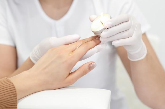 Mestre de manicure aplicando cera quente de vela nas unhas de uma jovem em um salão de beleza
