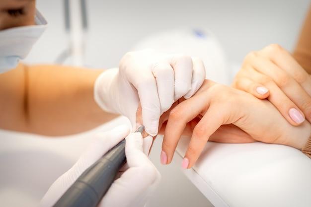 Mestre de manicure aplicando máquina elétrica de lixa de unha removendo esmalte velho das unhas em um salão de beleza