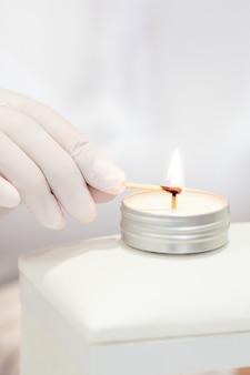 Mestre de manicure com luvas brancas acendendo vela com fósforo no salão de manicure