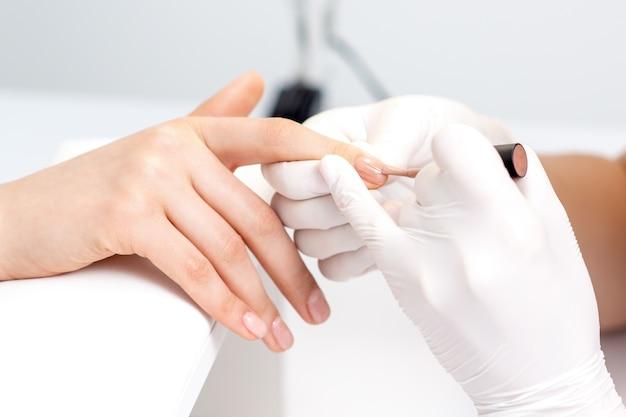Mestre de manicure com luvas de proteção aplicando esmalte bege nas unhas femininas no salão de beleza