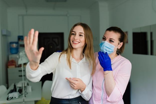 Mestre de manicure feminina em um salão de beleza trabalha com as mãos da cliente