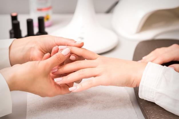 Mestre de manicure massageando os dedos femininos de clientes depois de polir as unhas em um salão de manicure