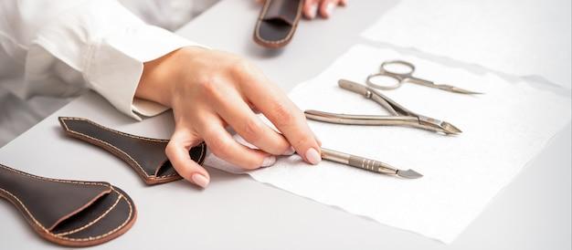 Mestre de manicure mostra conjunto de manicure em uma toalha na mesa em um salão