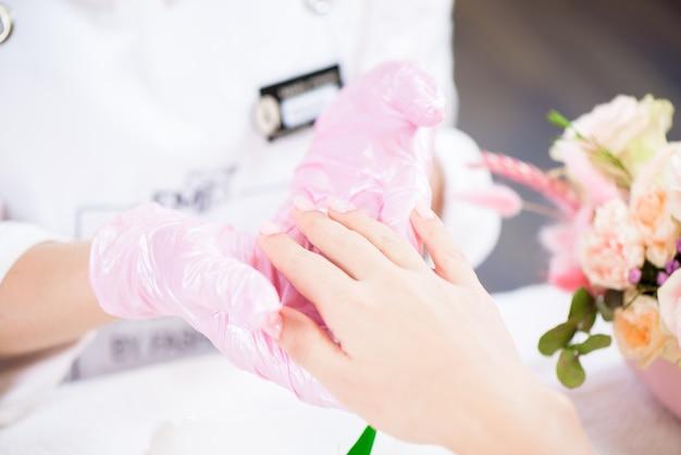 Mestre de manicure segurando as mãos femininas em um salão de beleza.