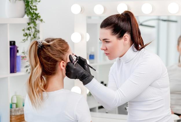 Mestre de maquiagem permanente desenhando o novo formato das sobrancelhas durante o processo de tatuagem com microblad