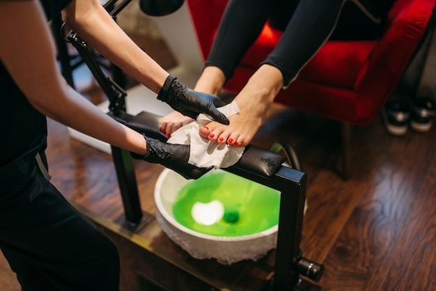 Mestre de pedicure em luvas pretas, fazendo procedimento cosmético, cliente do sexo feminino no salão de beleza.