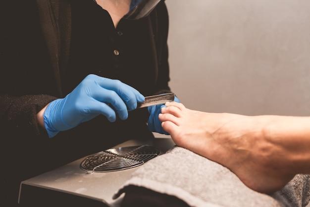 Mestre de pedicure lixa as unhas com uma lixa de unha para aplicação posterior de verniz