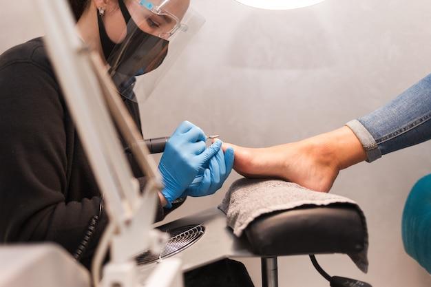 Mestre de pedicure polonês unhas com broca de lixa de unhas antes de aplicar verniz lateral