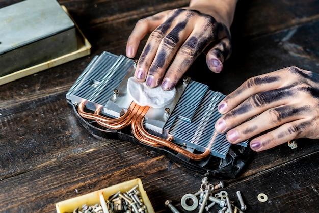 Mestre de reparo do computador com as mãos sujas escuras, limpeza da peça eletrônica em cima da mesa