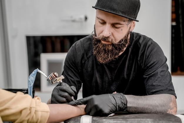 Mestre de tatuagem masculina cliente feminina de tatuagem. máquina de tatuagem e lâmpada. artista no local de trabalho. criando uma imagem disponível com ela no salão.