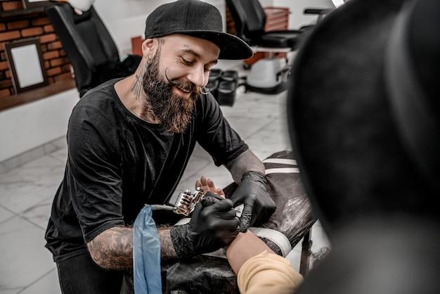 Mestre de tatuagem masculina sorrindo cliente feminina de tatuagem. máquina de tatuagem e lâmpada. artista no local de trabalho. criando uma imagem disponível com ela no salão.
