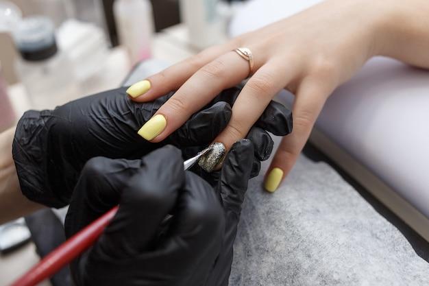 Mestre de unhas usando luvas pretas, aplicando o pincel nas unhas de acrílico