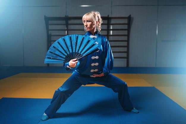 Mestre de wushu feminino com leque, artes marciais. mulher vestida de azul em treino de luta