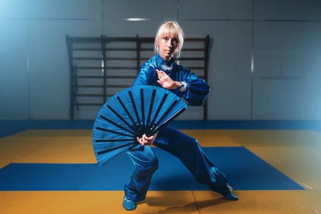 Mestre de wushu feminino com leque, artes marciais