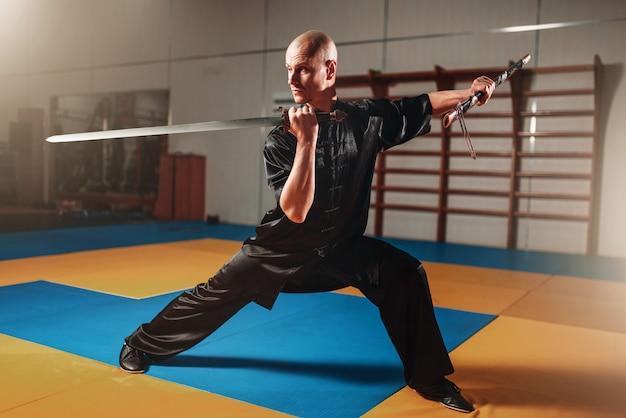 Mestre de wushu treinando com espada, artes marciais. homem de pano preto posa com lâmina