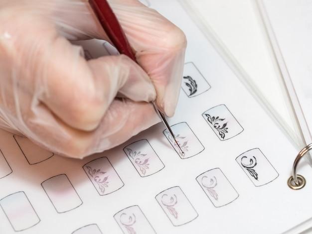 Mestre desenha um monograma. treinamento em monogramas de pintura para manicure
