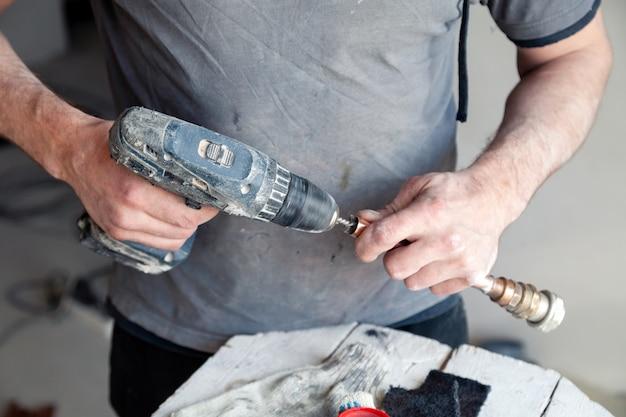 Mestre do encanador do trabalhador do close up que limpa as tubulações de cobre com a escova profissional.