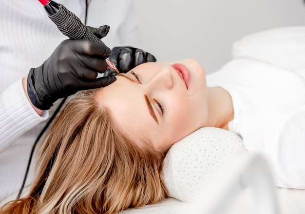 Mestre em fazer a maquiagem definitiva de sobrancelhas loiras usando máquina de tinta profissional