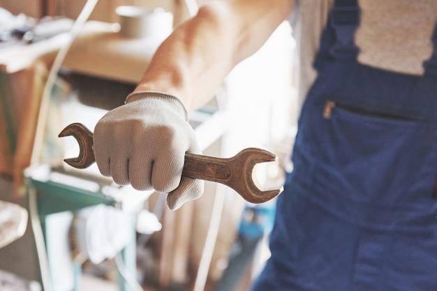 Mestre em forma de trabalho e luvas com uma chave nas mãos.