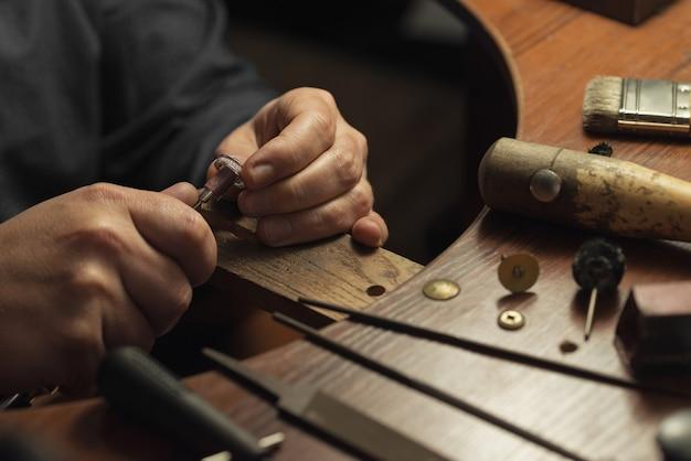 Mestre em joalheria polindo manualmente anel de ouro com mesa de trabalho de diamantes para fabricação de joias artesanais ...