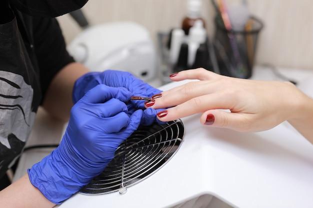 Mestre em luvas de proteção durante uma manicure no salão de beleza