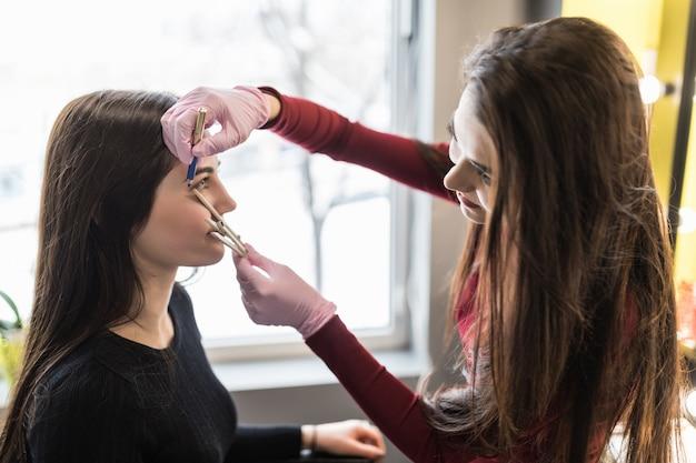 Mestre em luvas de trabalho na técnica de sobrancelhas balck no salão de beleza