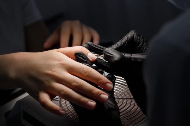 Mestre em salão de beleza faz close-up de manicure