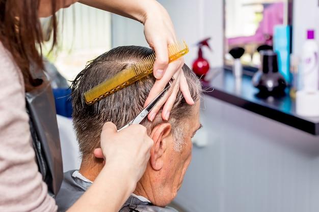 Mestre em salão de cabeleireiro faz penteado elegante para um homem idoso