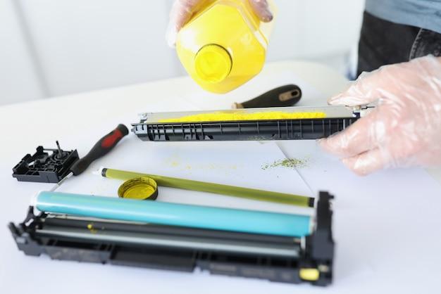 Mestre está derramando tinta no cartucho para close-up da impressora