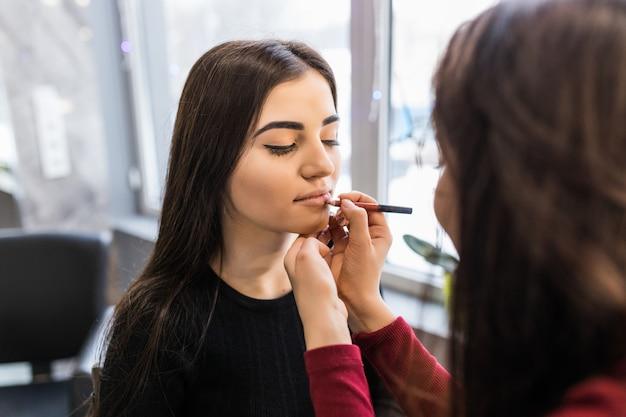 Mestre está pintando os lábios da jovem modelo antes da sessão de fotos