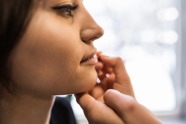Mestre está pintando os lábios da jovem modelo antes de fotografar à noite