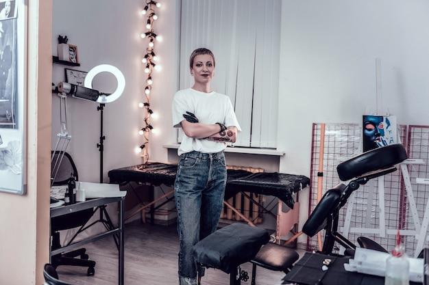 Mestre extraordinário de cabelos curtos. mulher tatuadora sorridente em pé em seu gabinete equipado e se sentindo orgulhosa de seu trabalho