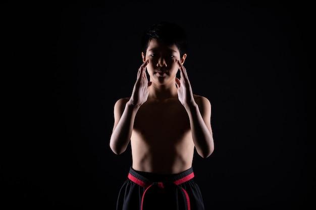 Mestre faixa preta vermelha taekwondo garoto de caratê que é atleta jovem adolescente mostra as tradicionais poses de luta em traje esporte, parede preta isolada cópia espaço, baixa exposição no escuro