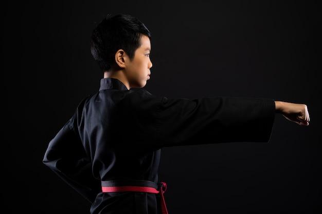 Mestre faixa preta vermelha taekwondo karate menino que é atleta jovem adolescente mostra as tradicionais poses de luta em vestido esporte, parede preta isolada cópia espaço