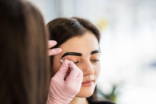 Mestre fazendo maquiagem com linhas de sobrancelha pretas
