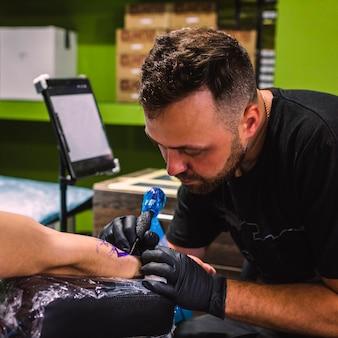 Mestre fazendo tatuagem com máquina de agulha