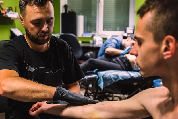 Mestre fazendo tatuagem no estúdio