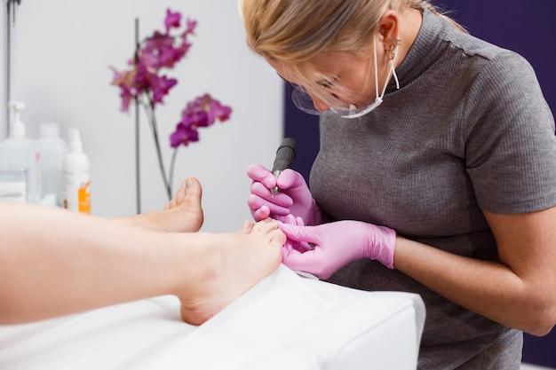 Mestre feminino fazendo pedicure para um cliente em um salão de beleza