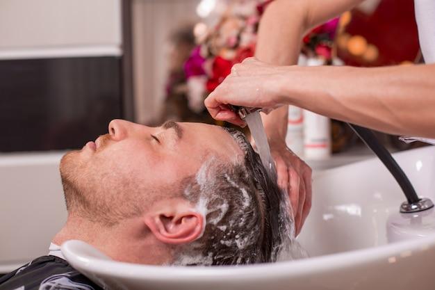 Mestre lava a cabeça do cliente na barbearia, cabeleireiro faz penteado para um jovem.