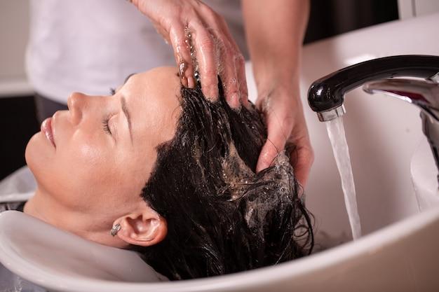 Mestre lava a cabeça do cliente na barbearia, cabeleireiro faz penteado para uma jovem.