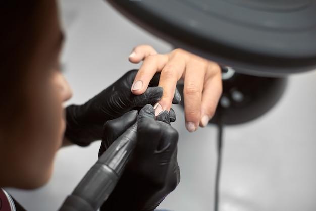 Mestre manicure profissional trabalhando nas unhas dos clientes