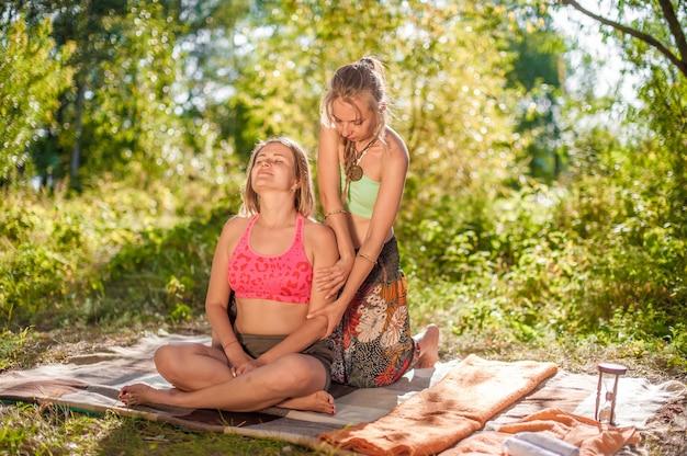 Mestre massoterapeuta aplica suas habilidades de massagem em seu cliente no solo da floresta
