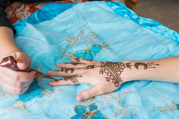 Mestre mehndi de tatuagem desenha na mão da senhora