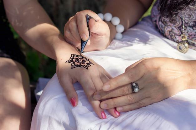 Mestre mehndi desenha henna em uma mão feminina