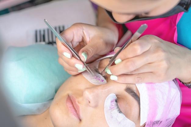 Mestre mulher no salão de beleza está trabalhando na extensão de cílios para o cliente