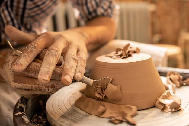 Mestre na arte da cerâmica, tornando as laterais da nova tigela de argila planas e lisas com uma ferramenta manual especial durante o trabalho