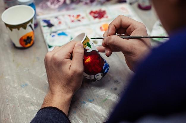 Mestre pintando em um copo de plástico