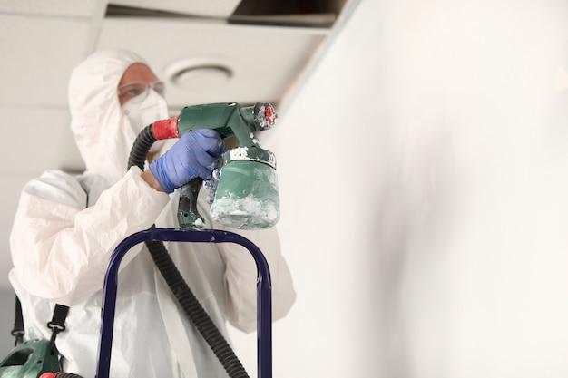 Mestre pintor em traje de proteção está tocando a parede com pistola de pulverização