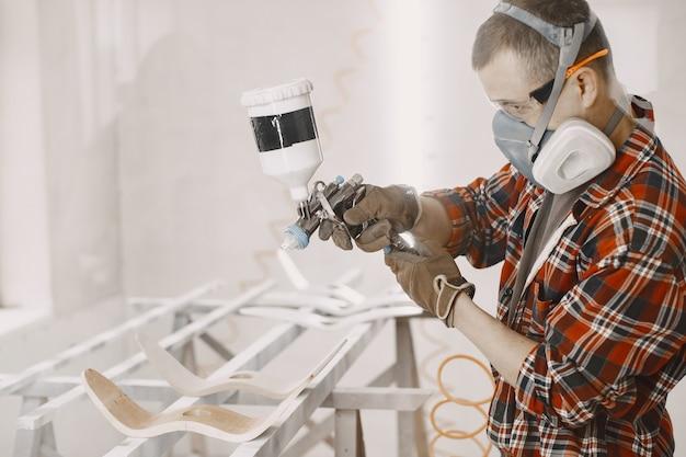 Mestre pintor em uma fábrica pintando madeira com pistola de pulverização
